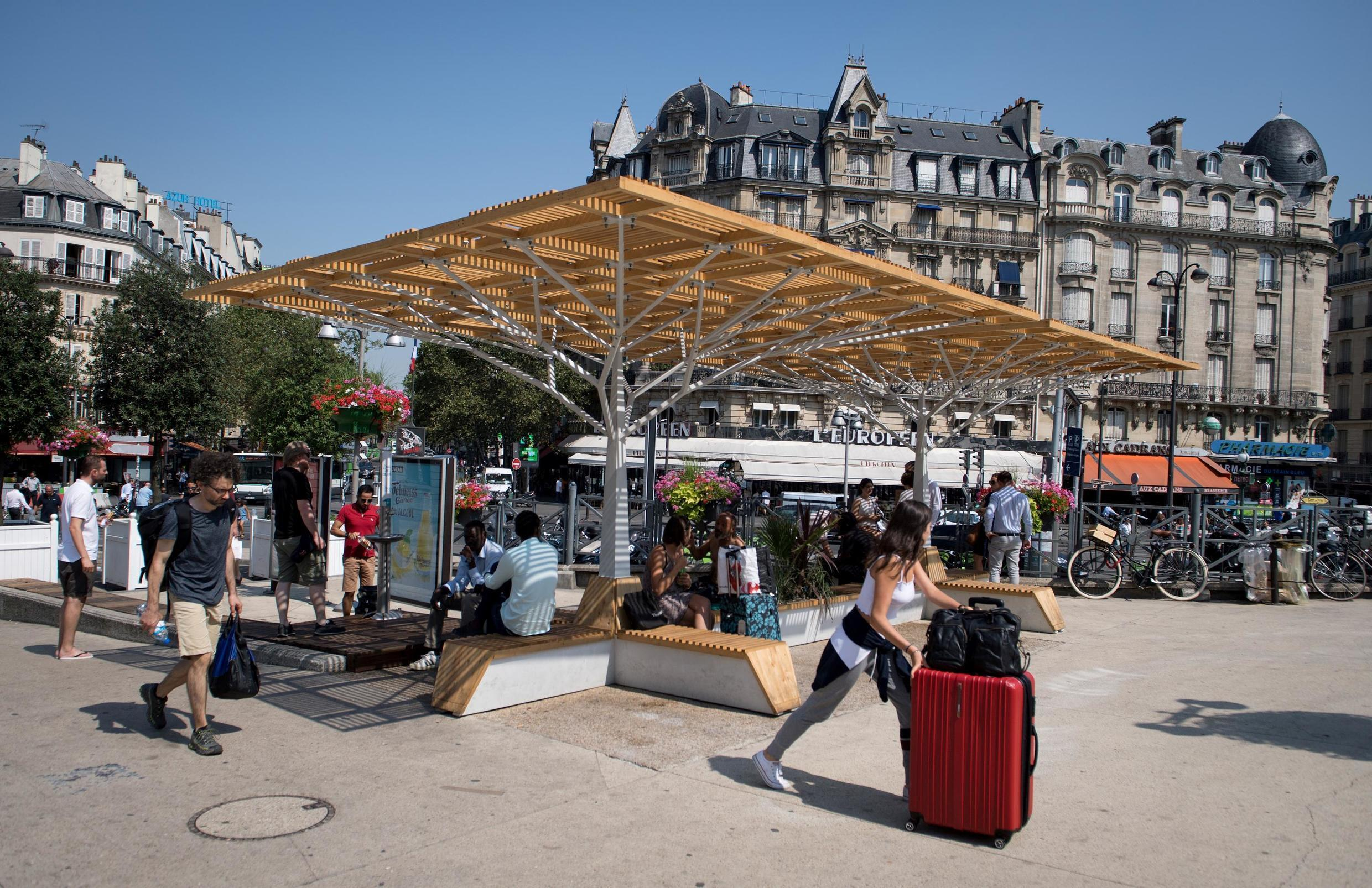 """People cool off below a """"Cooling Island"""", designed by Climespace and installed in partnership with the SNCF and Eau de Paris in Gare de Lyon in Paris on 26 July, 2018."""