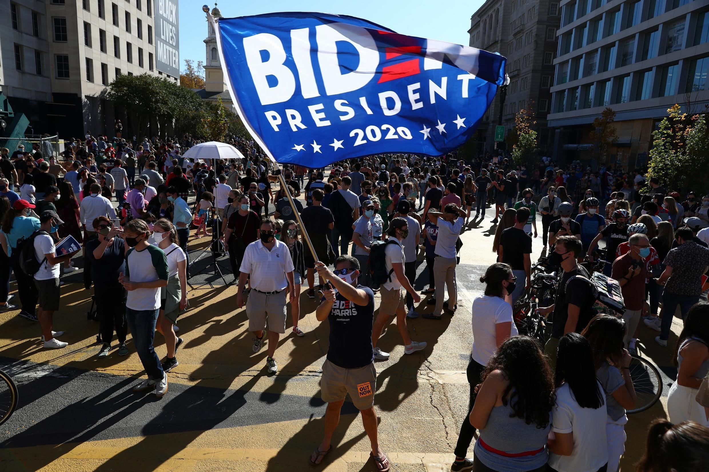 Un homme agite un drapeau Biden au Black Lives Matter Plaza après l'annonce de la victoire de Joe Biden à la présidentielle américaine de 2020,  à Washington le 7 novembre 2020.