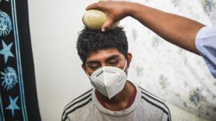 Un chamán pasa un huevo de avestruz sobre la cabeza de un hombre durante un ritual de predicciones en el Mercado de los Deseos en Lima, el 30 de diciembre de 2020,en medio de la pandemia de coronavirus en Perú.