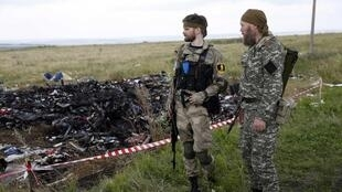 Armed pro-Russian separatists stand guard at the crash site of Malaysia Airlines Flight MH17, Donetsk region, 22 July 2014.