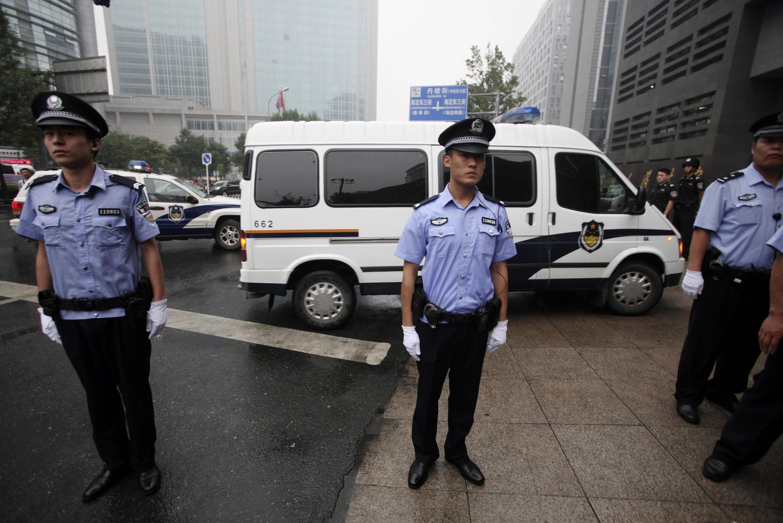 Xe cảnh sát áp giải Lý Thiên Nhất đến toà án Bắc Kinh - REUTERS /China Daily