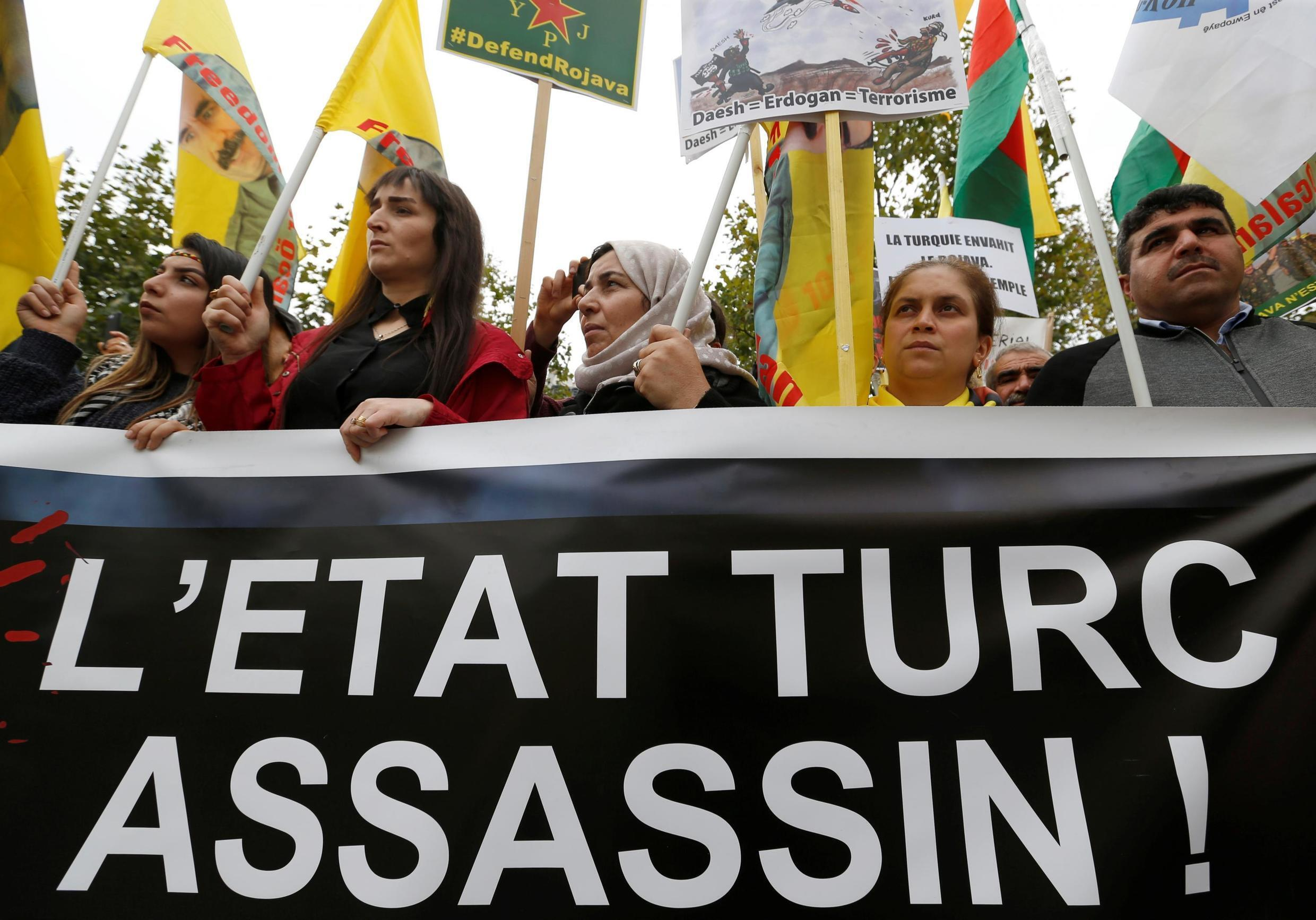"""Kurdish protesters hold a banner reading """"Turkish state murderer"""" as they attend a demonstration against Turkey's military action in northeastern Syria, in Paris, France, October 12, 2019"""