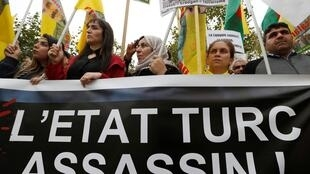 "Kurdish protesters hold a banner reading ""Turkish state murderer"" as they attend a demonstration against Turkey's military action in northeastern Syria, in Paris, France, October 12, 2019"