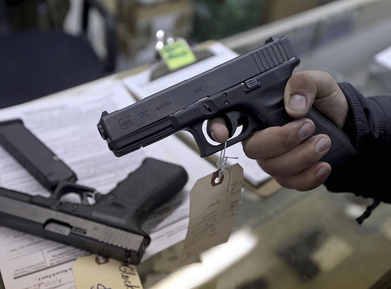 A customer looks over a Glock 17 9mm hand gun in a gun shop, Phoenix, Arizona