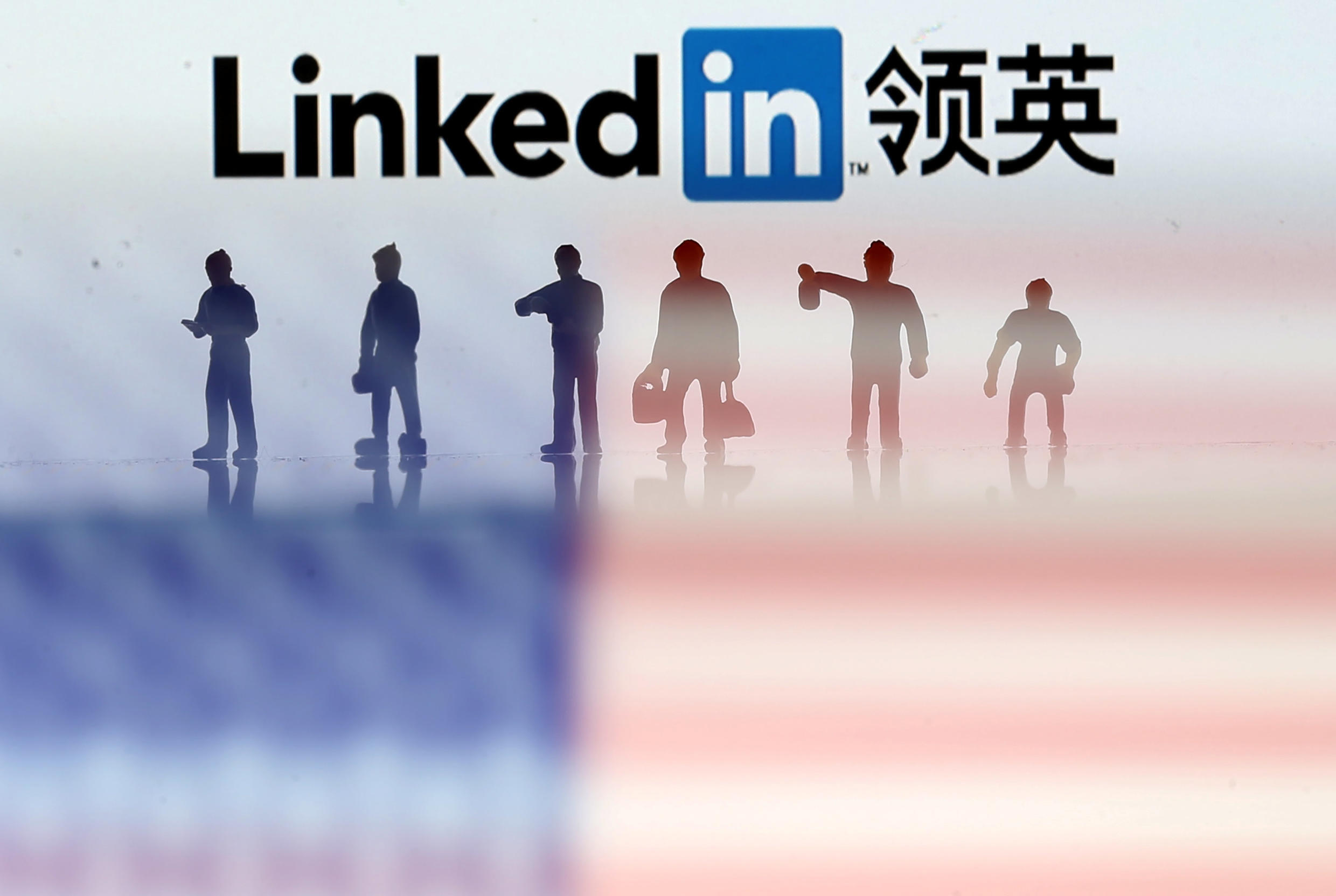 Small toy figures are seen between displayed U.S. flag and Linkedin logo in this illustration picture, August 30, 2018