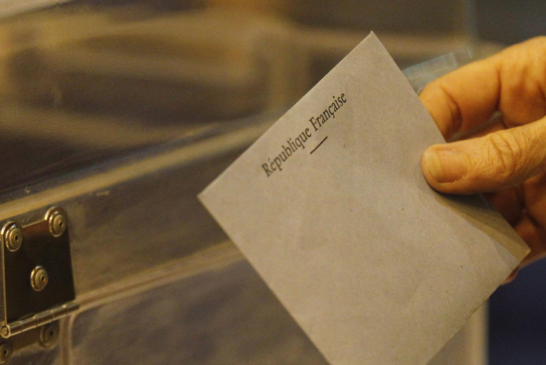 Eleitor deposita voto em urna francesa.