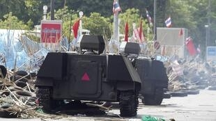 Armoured vehicles drive over wreckage from a barricade