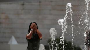 Mulher se refresca em chafariz de Lisboa, onde parques públicos foram fechados por causa do calor.