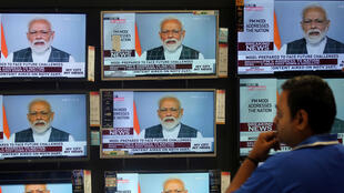 A man watches Prime Minister Narendra Modi addressing to the nation on TV screens inside a showroom in Mumbai, India, March 27, 2019. REUTERS/Francis Mascarenhas