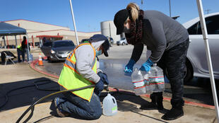People help fill jugs at a drive-through water distribution center at a high school in Kyle, Texas on February 20, 2021