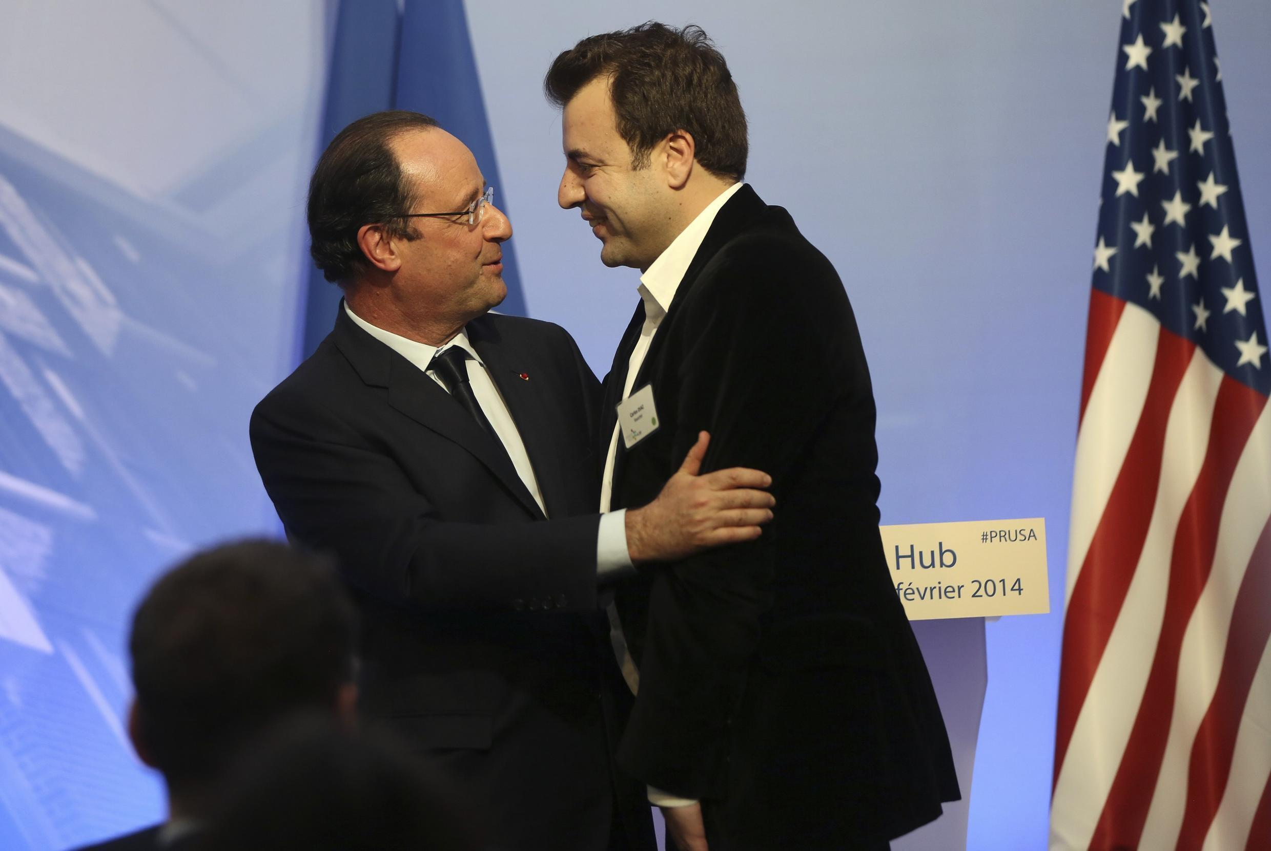 French President Francois Hollande (L) embraces CEO and co-founder of Kwarter Carlos Diaz on his visit to Silicon Valley