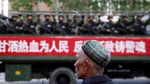 Un hombre uigur mira un camión con policía paramilitar en la regioón de Xinjiang, el 23 de mayo de 2014.