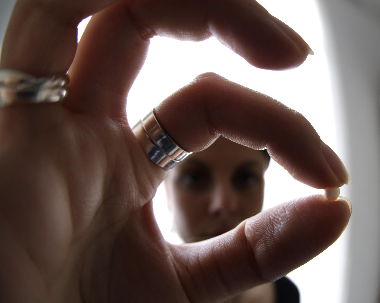 Uma usuária francesa mostra uma pílula anticoncepcional de última geração