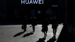北京,12月11日,人們經過華為商店。
