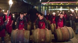 Men roll barrels of Beaujolais Nouveau wine for the official launch of the 2011 vintage