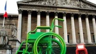 Một chiếc xe lăn màu xanh lá cây được đặt bên ngoài tòa nhà Quốc Hội Pháp, Paris, ngày 26/01/2012.