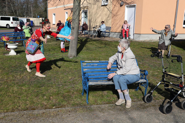 Клоун Таня Селмер выступает для пожилых людей в доме престарелых в Йютербоге, к югу от Берлина, Германия, 7 апреля 2020 года.