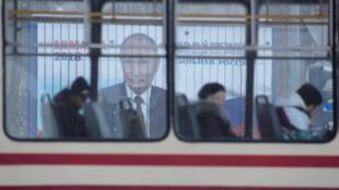Un autobus con pasajeros delante de un cartel con la imágen de Vladimir Putin, San Petesburgo, 19 febrero 2018