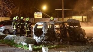 Firefighters in the French city of Grenoble extinguish a car set ablaze during riots sparked after the deaths of two youths fleeing police.