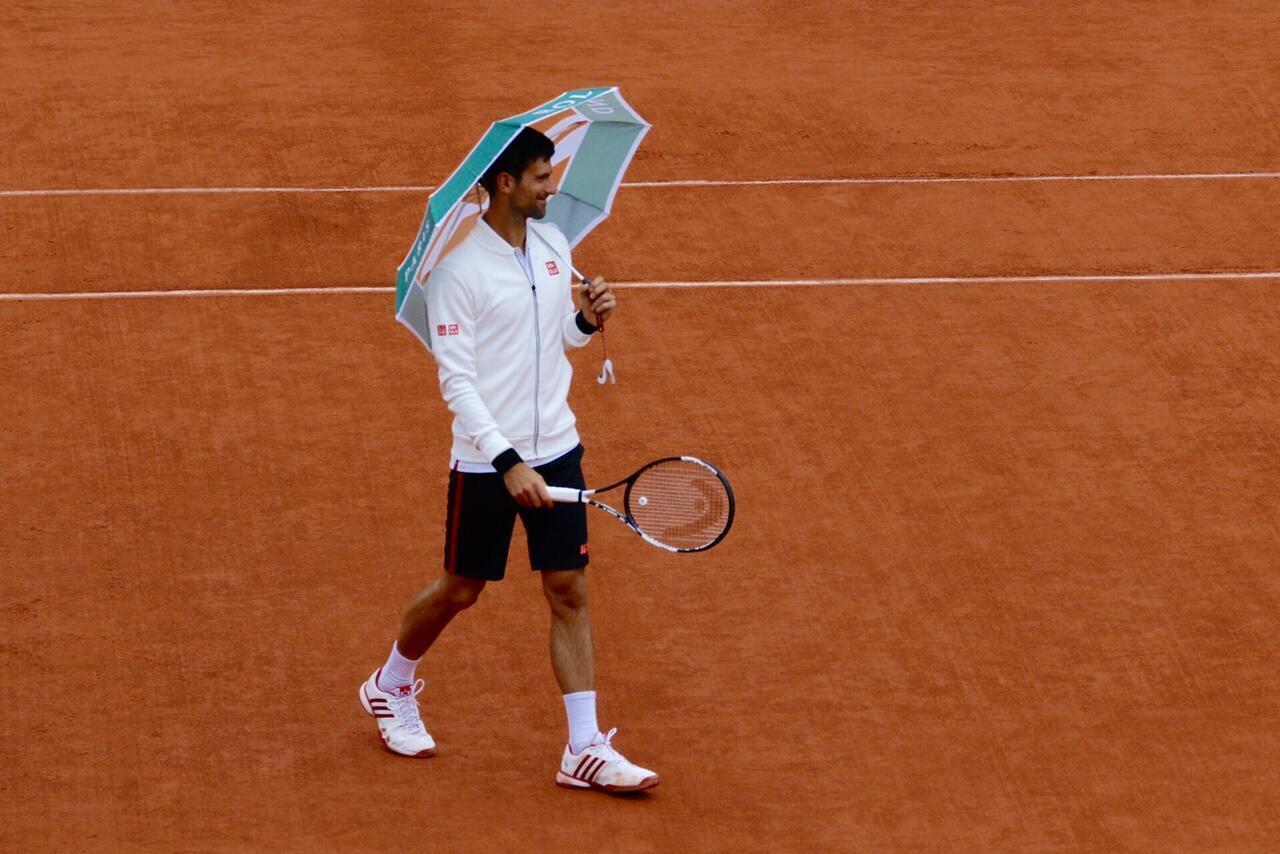 Novak Djokovic de guarda-chuva na quadra principal de Roland Garros.