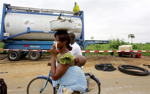 Une femme et son enfant passent à proximité d'employés d'une firme qui tentent de dépolluer la zone touchée par le rejet des déchets toxiques du Probo koala, près d'Abidjan.