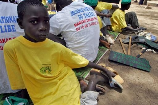 """A """"Talibe"""", pupil from a Koranic school, takes a break next to a placard reading in French """"No begging for children"""""""