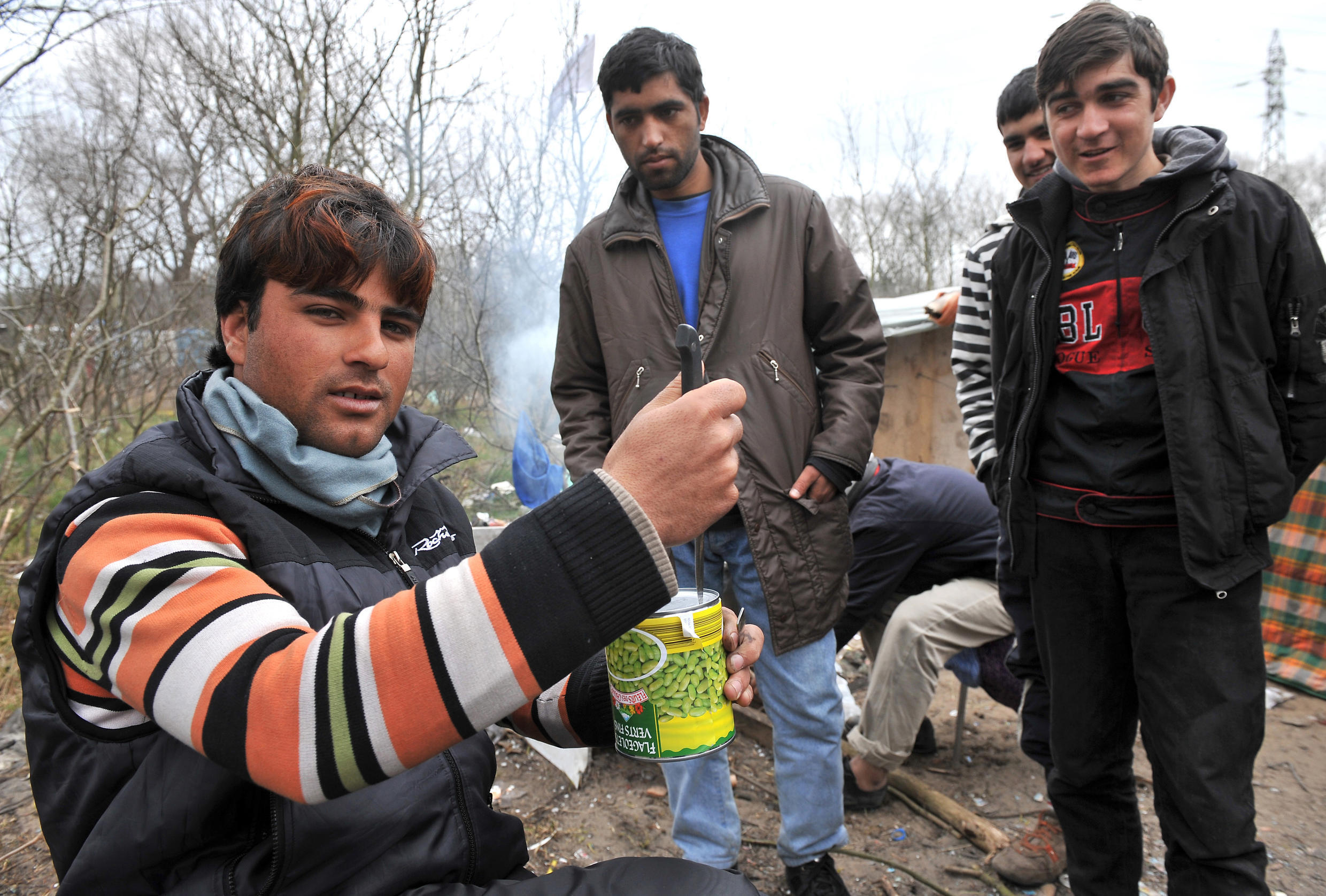 23 March 2009 - Afghan men prepare their meal in 'the Jungle' in Calais.