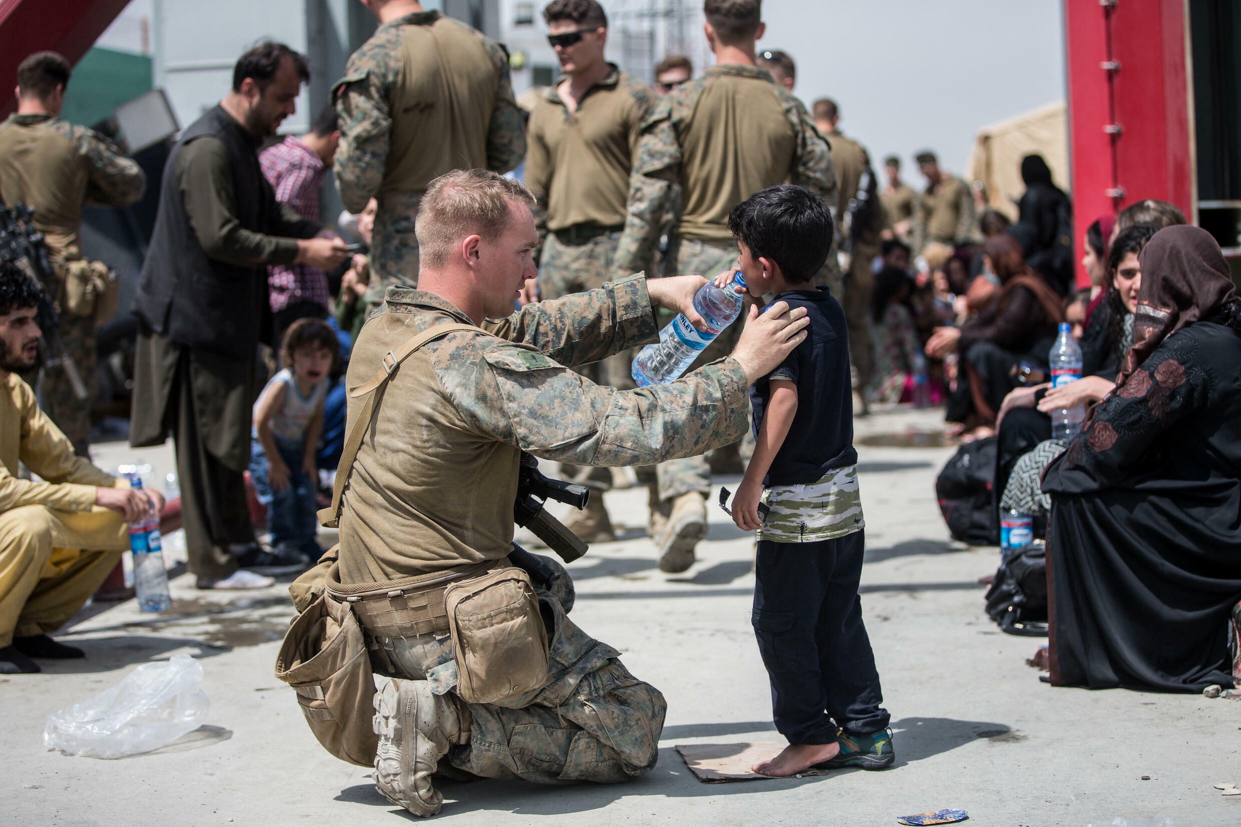 On August 20, 2021, a U.S. Navy man gives fresh water to a baby at Kabul Airport