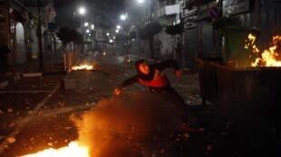 Un Palestinien jette des pierres vers les troupes israéliennes lors d'échauffourées à Ramallah, en Cisjordanie, le 22 juin 2014.