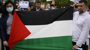 Un par de albanokosovares exhiben una bandera palestina mientras marchan por las calles de Pristina, Kosovo, el 14 de mayo de 2021, pidiendo el fin de la violencia en la Franja de Gaza.