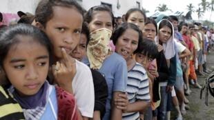 Desabrigados do Vale de Compostela fazem fila para receber ajuda num centro de atendimento do governo na localidade de New Bataan, no sul das Filipinas.