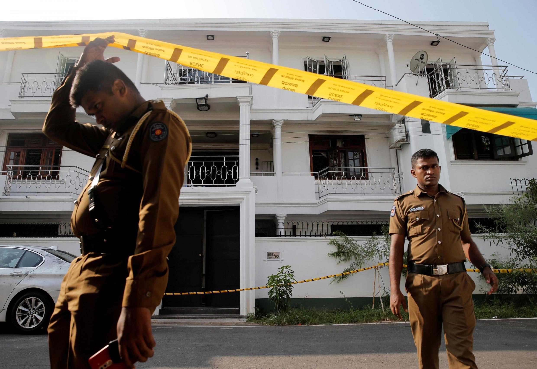 Des policiers sri-lankais devant la maison de la famille de l'un des suspects des attentats de Pâques, à Colombo. Le 25 avril 2019.