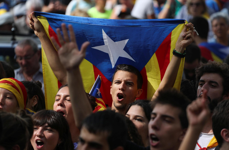 Manifestantes enarbolan la bandera independentista catalana.