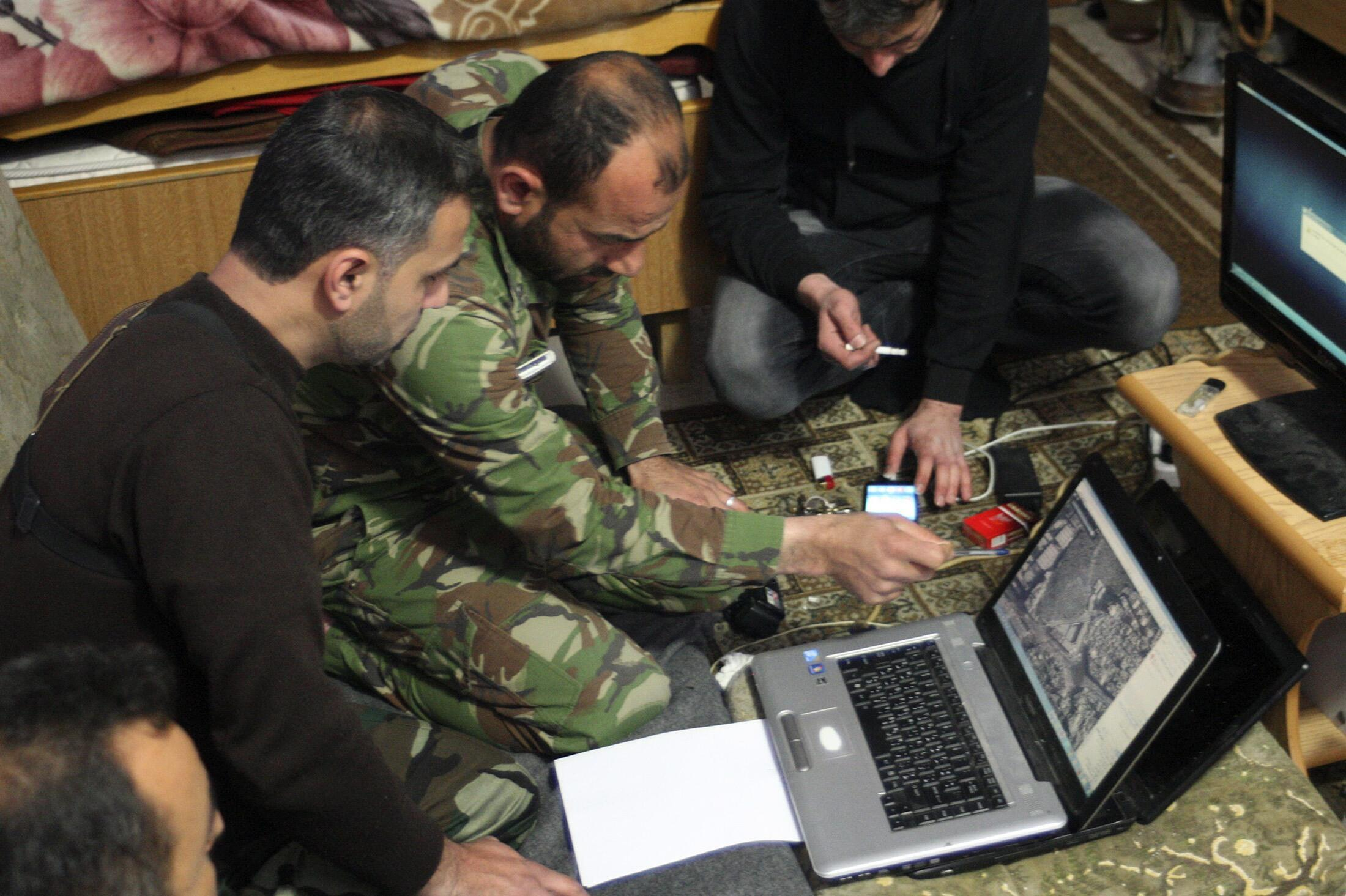 Des soldats de l'Armée syrienne libre étudient une carte sur un ordinateur, à Alep. Une société française est accusée d'avoir fournit du matériel de surveillance informatique au régime de Bachar el-Assad.