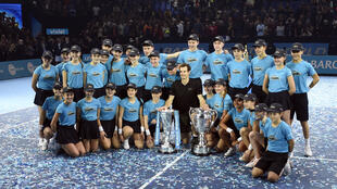 Andy Murray celebrates his prizes with ball boys and ball girls at the ATP Tour Finals in London.