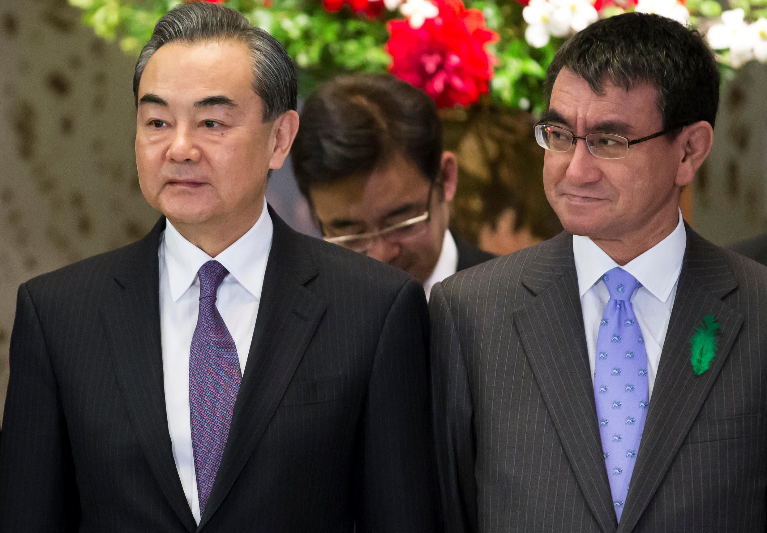 Wang Yi, China's foreign minister, and Taro Kono, Japan's foreign minister, pose during a photo session ahead of a high-level Japan-China economic dialogue in Tokyo, Japan, April 16, 2018. Tomohiro Ohsumi/Pool via Reuters