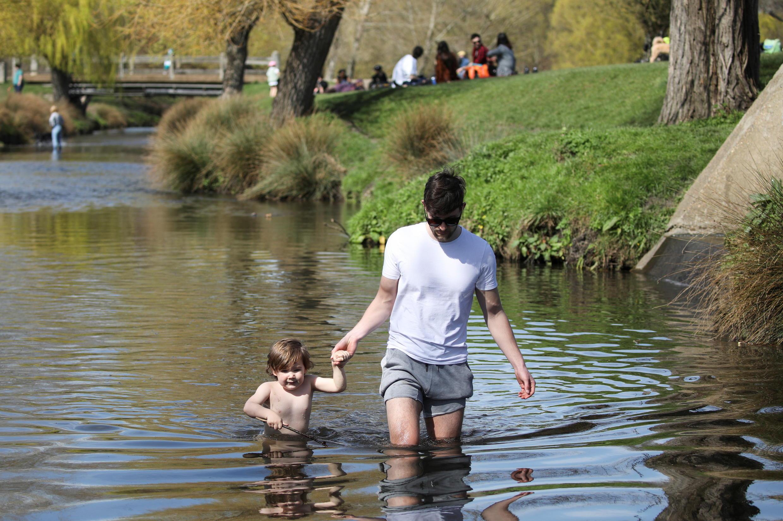 Un hombre y un niño caminan en el agua en Richmond Park, Londres, Gran Bretaña, el 30 de marzo de 2021.