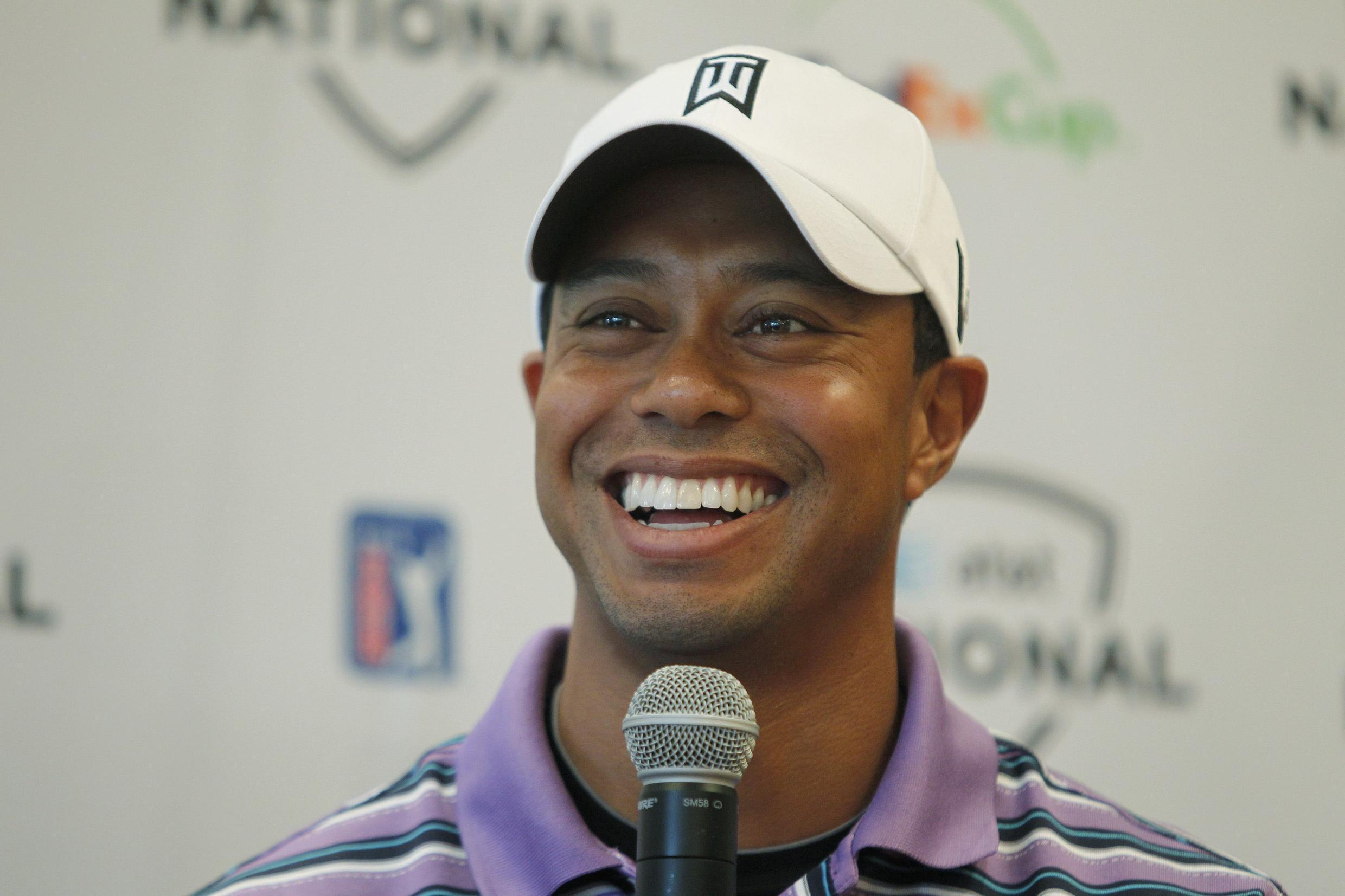 Tiger Woods smiles during a news conference to promote the AT&T National golf tournament at the Aronimink Golf Club in Newtown Square, 2011.