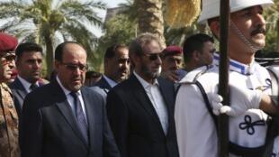 Nouri al-Maliki, à gauche, aux côtés de son ministre de la Défense, lors d'une cérémonie de funérailles militaires à Bagdad, le 7 juillet 2014.