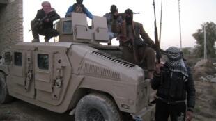 Des sunnites irakiens en arme posent devant un véhicule de l'armée, le 9 janvier 2014 à Fallouja.