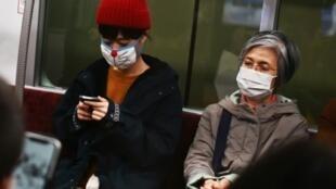 Dans le métro, des habitants de Tokyo portent des masques. Au moins 156 personnes ont été infectées par le Covid-19 dans l'archipel nippon