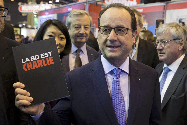 Presidente francês recebeu livro em homenagem a chargistas do Charlie Hebdo.