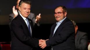 El presidente Juan Manuel Santos y el jefe de las FARC al momento de la firma del acuerdo de paz el 24 de noviembre.
