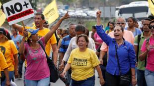 Des manifestants qui brandissent des pancartes ou l'on peut lire «Plus de dictature» contre le gouvernement du président Maduro, le 31 mars 2017.