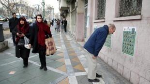 Dans une Rue de Téhéran, un homme regarde une affiche de la campagne électorale pour les législatives de ce vendredi 21 février 2020.