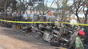 Police tape cordons off the area where the carcass of a burnt out fuel tanker is seen along the side of the road following an explosion on 10 August, 2019, in Morogoro, Tanzania.
