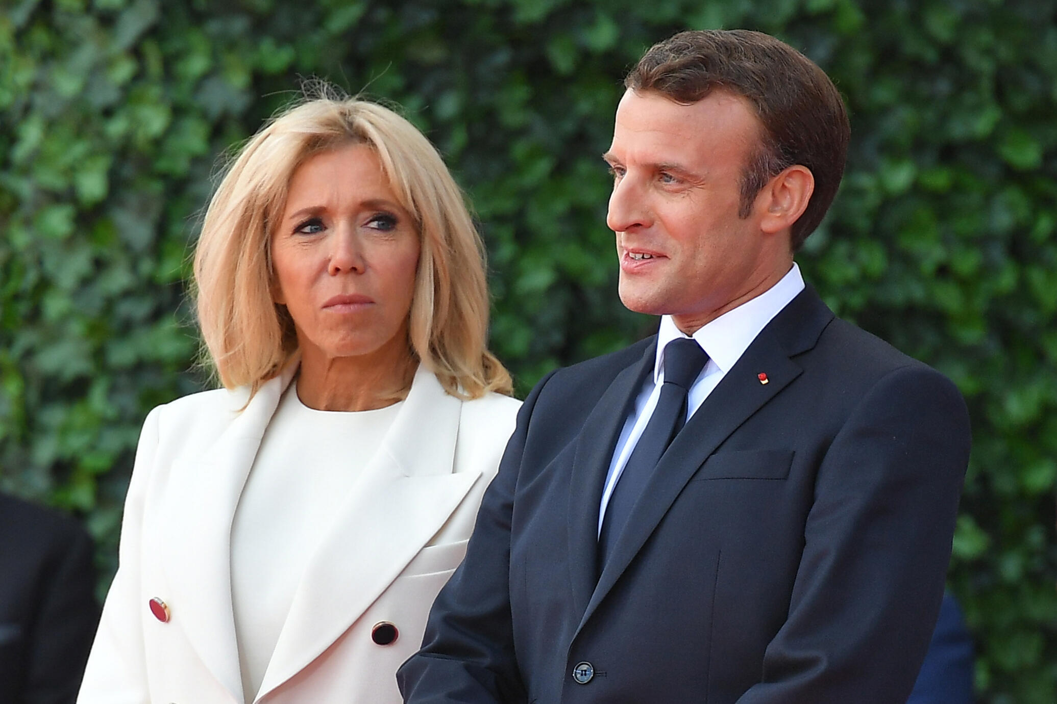 French President Emmanuel Macron (R) and French President's wife Brigitte Macron attend a French-US ceremony at the Normandy American Cemetery and Memorial in Colleville-sur-Mer, France, on June 6, 2019