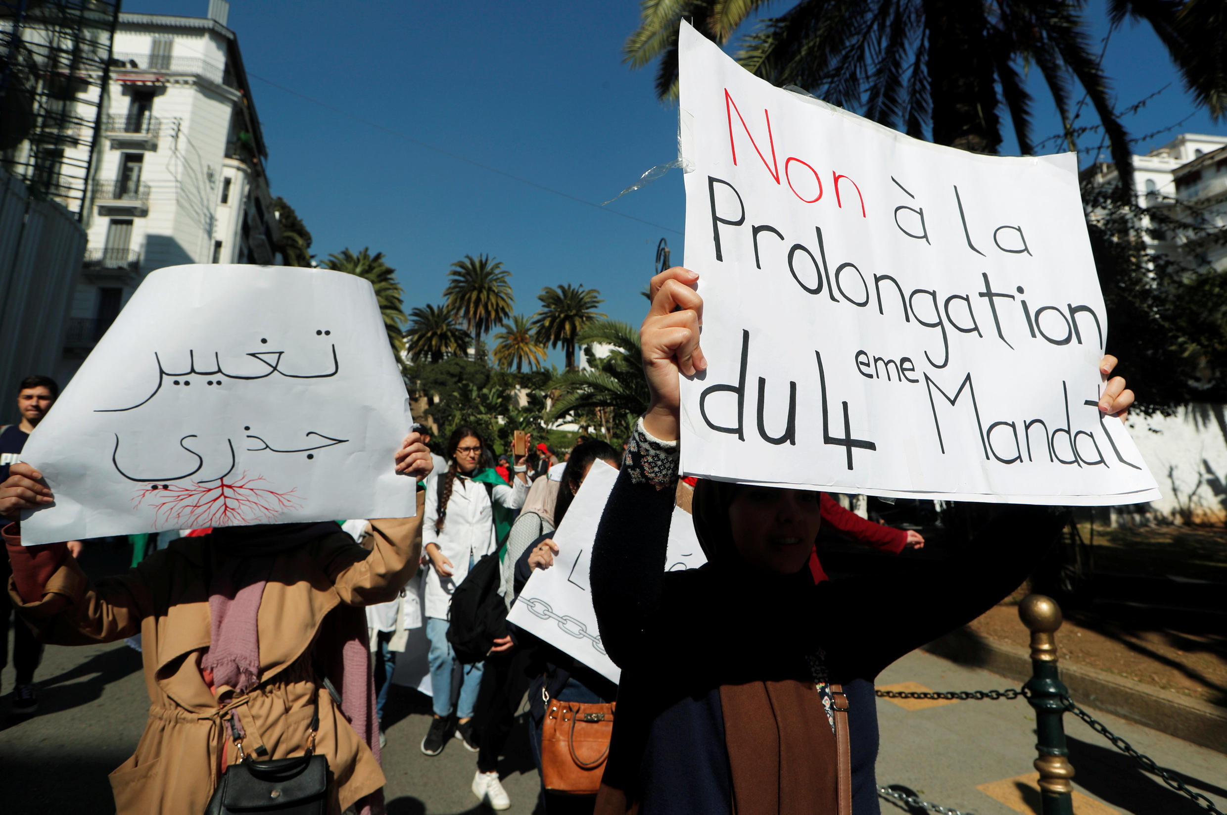 """People take part in a protest demanding immediate political change in Algiers on March 12, 2019. Signs read """"Radical change"""" and """"No extension to the 4th term""""."""