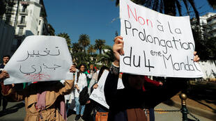 "People take part in a protest demanding immediate political change in Algiers on March 12, 2019. Signs read ""Radical change"" and ""No extension to the 4th term""."