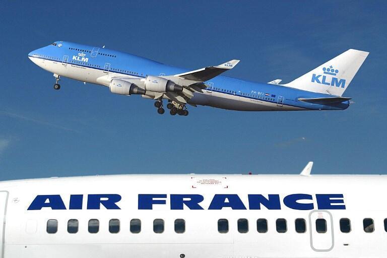 Un avion aux couleurs de la compagnie KLM vole au-dessus d'un avion d'Air France à l'aéroport Schipol à Amsterdam, le 1er janvier 2003.